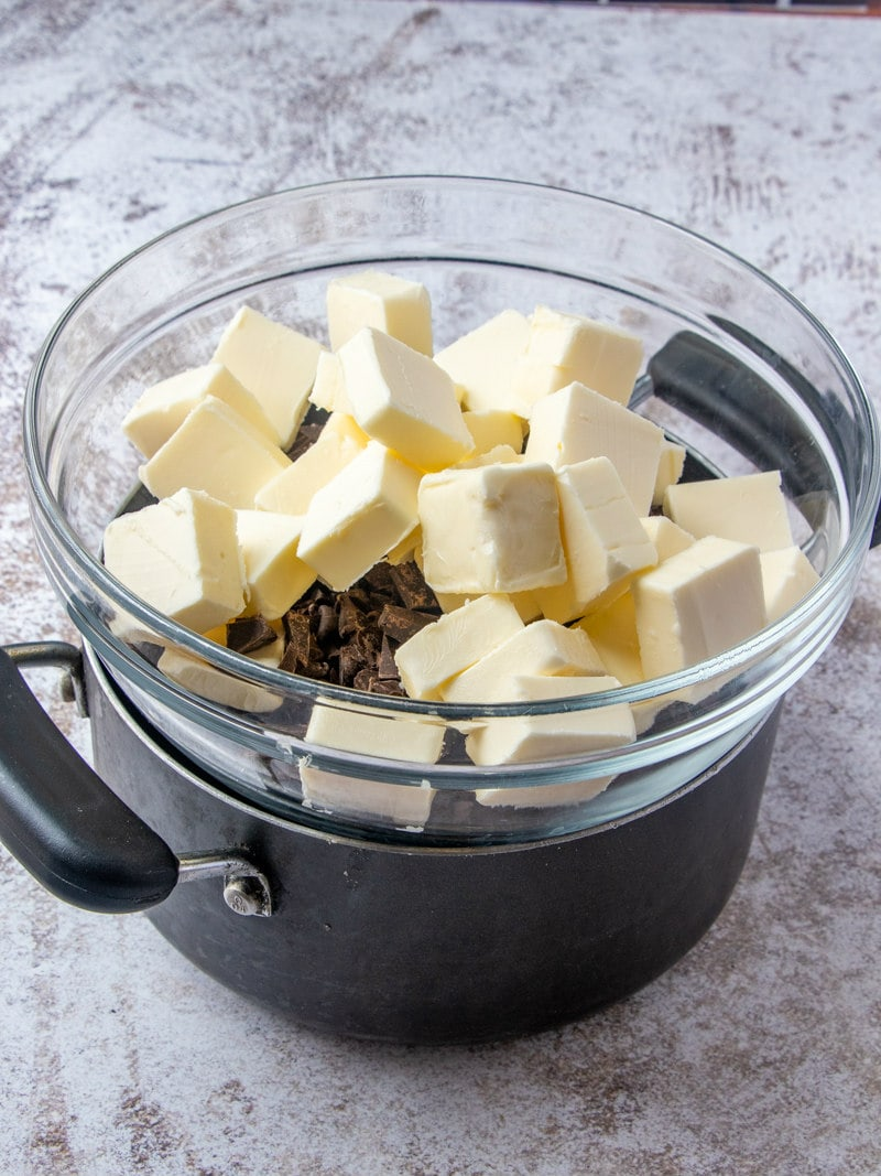 showing a pot with a glass bowl placed on top of it. Bowl is filled with butter and chocolate chips.