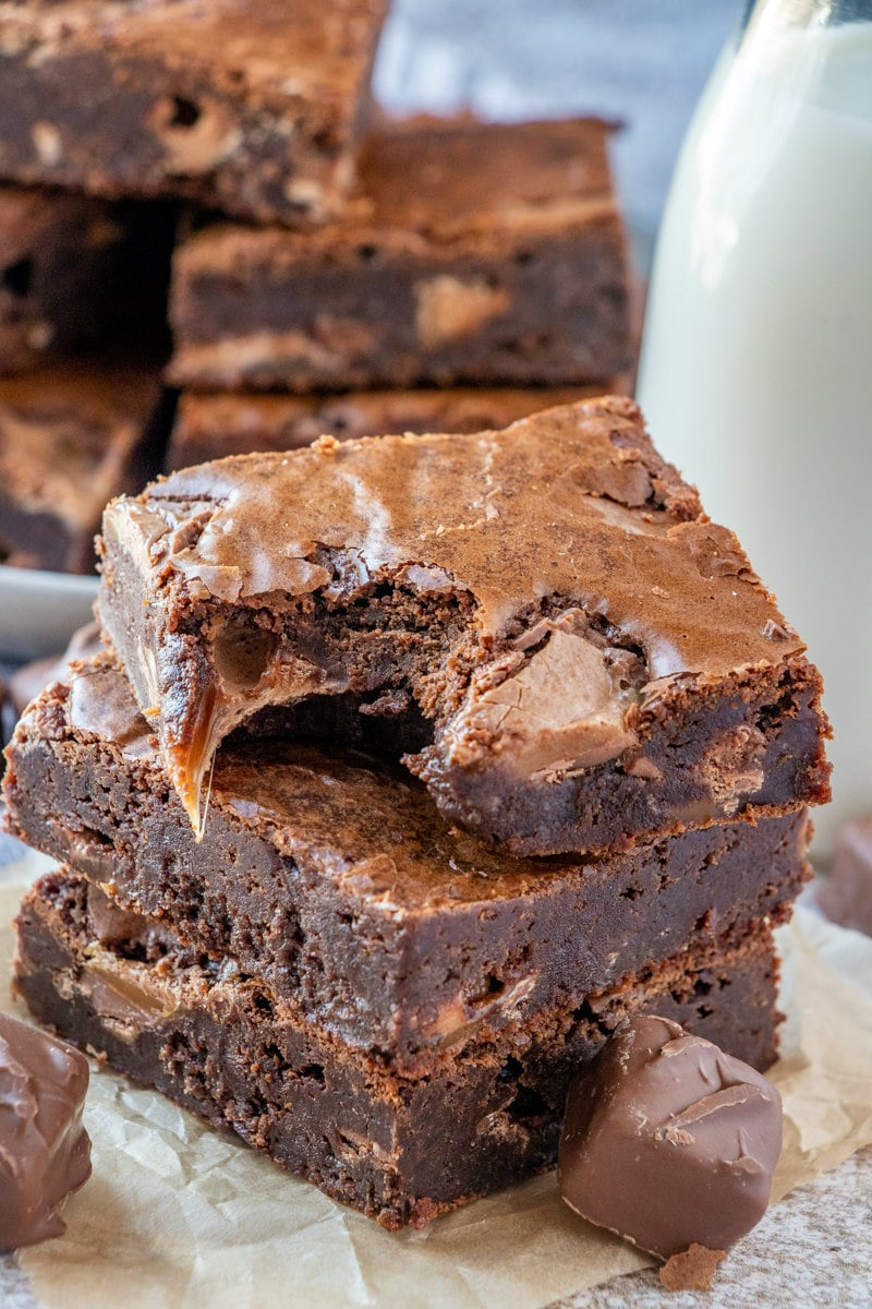 stack of three milky way brownies with a bite taken out of the one on top