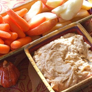 apple spice hummus in a serving dish with fresh vegetables served on the side