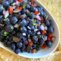 blueberry salsa in a white bowl surrounded by tortilla chips on a white/blue striped napkin
