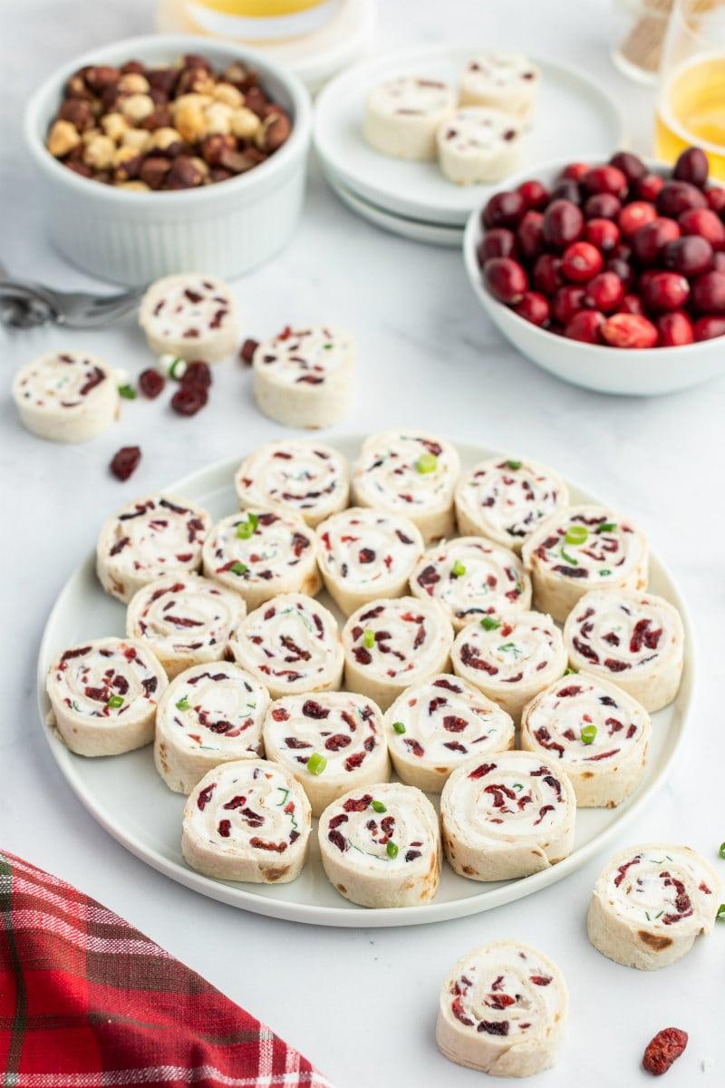 cranberry feta pinwheels on white platter displayed on appetizer table