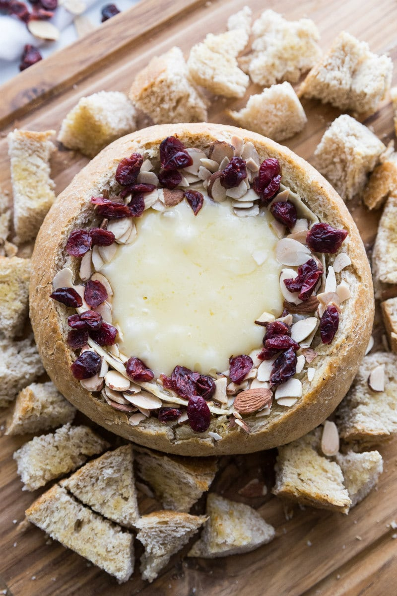 Baked Brie in a bread bowl with sliced almonds and dried cranberries