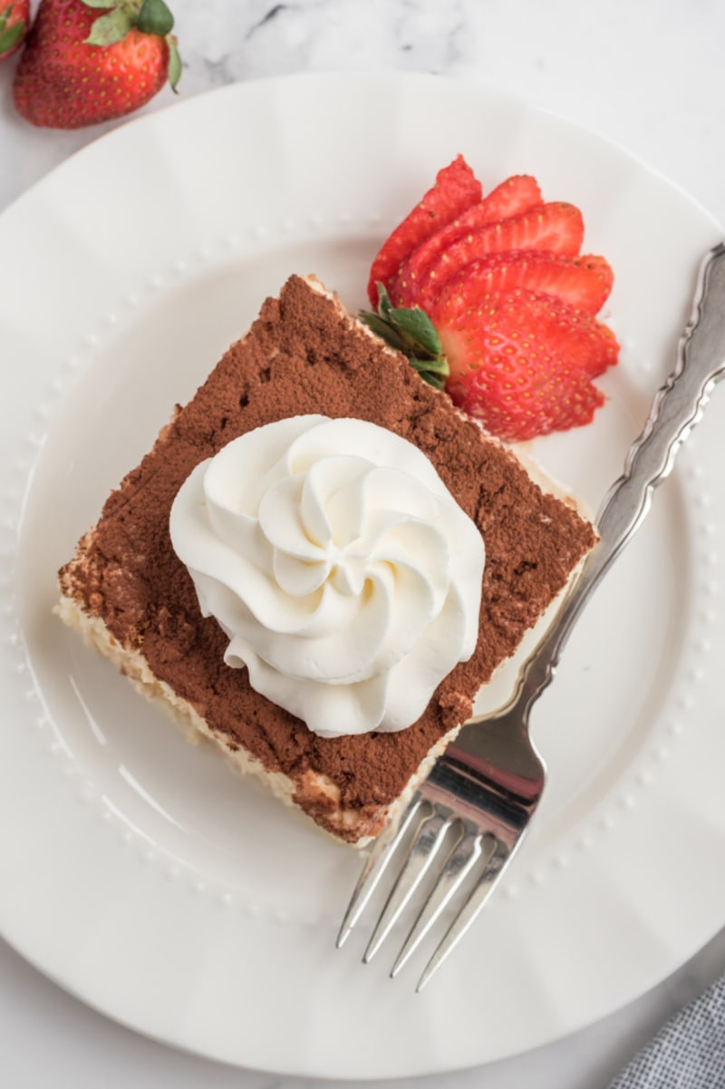 Slice of tres leches cake on a white plate with whipped cream and strawberries