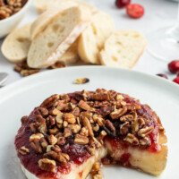 cranberry baked brie displayed with a wedge taken out of it
