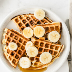 white plate with banana sour cream waffles. Sliced bananas on top