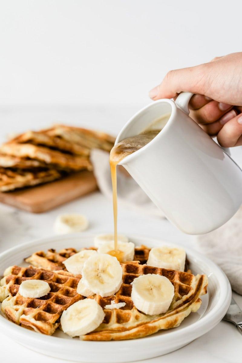 pouring syrup onto banana sour cream waffles with sliced banana on top