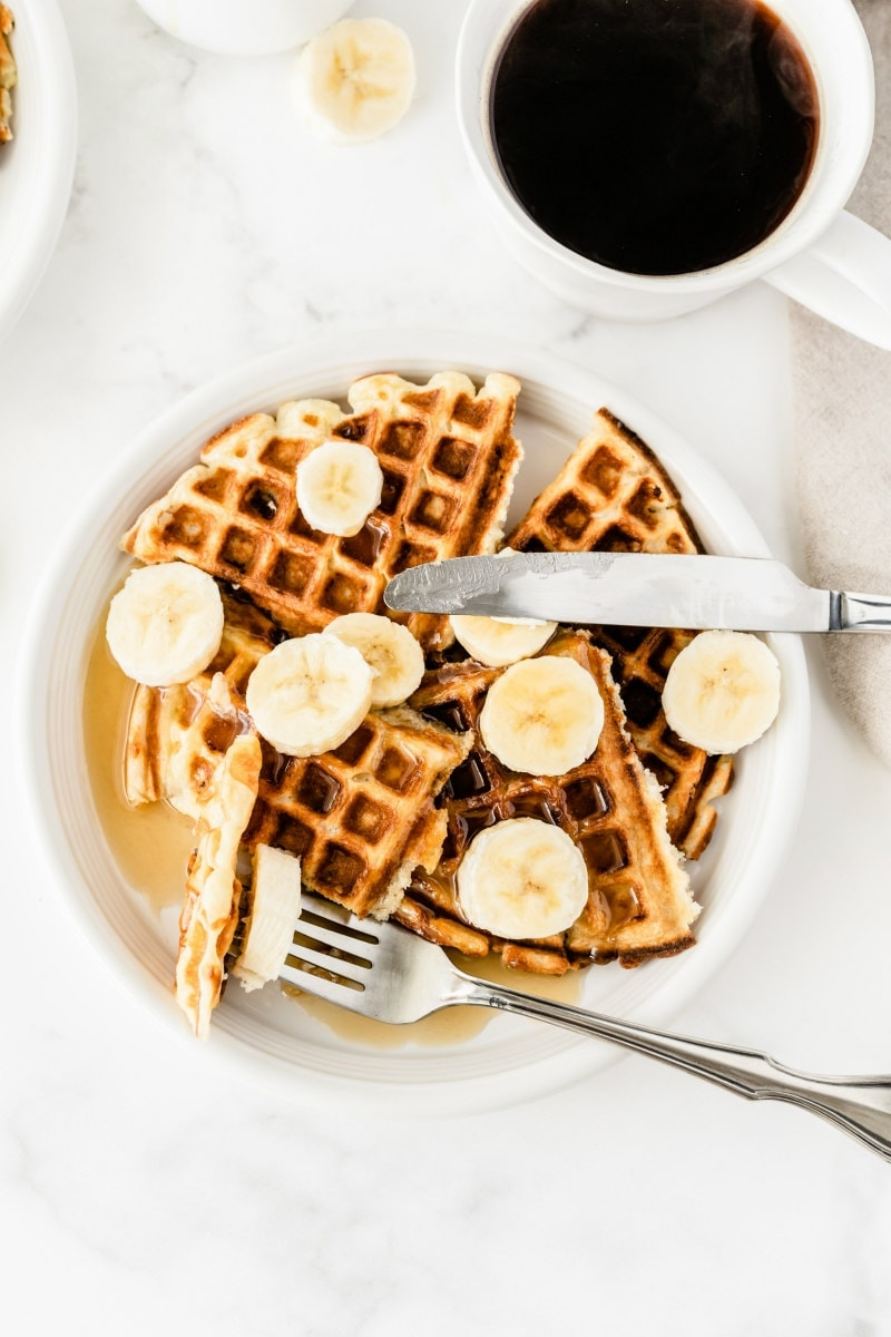 banana waffles on a white plate with a forkful of waffle and sliced bananas on top. Cup of coffee in the background
