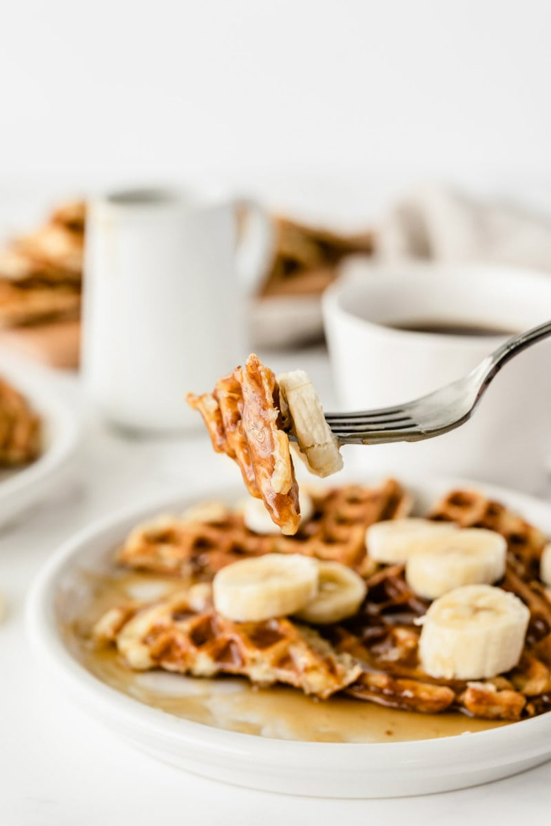 forkful of waffle above a plate of banana waffles. Cups of coffee in the background