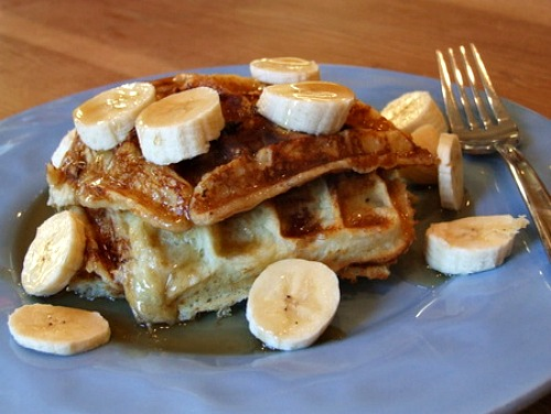 Banana Waffles on a blue plate topped with banana slices