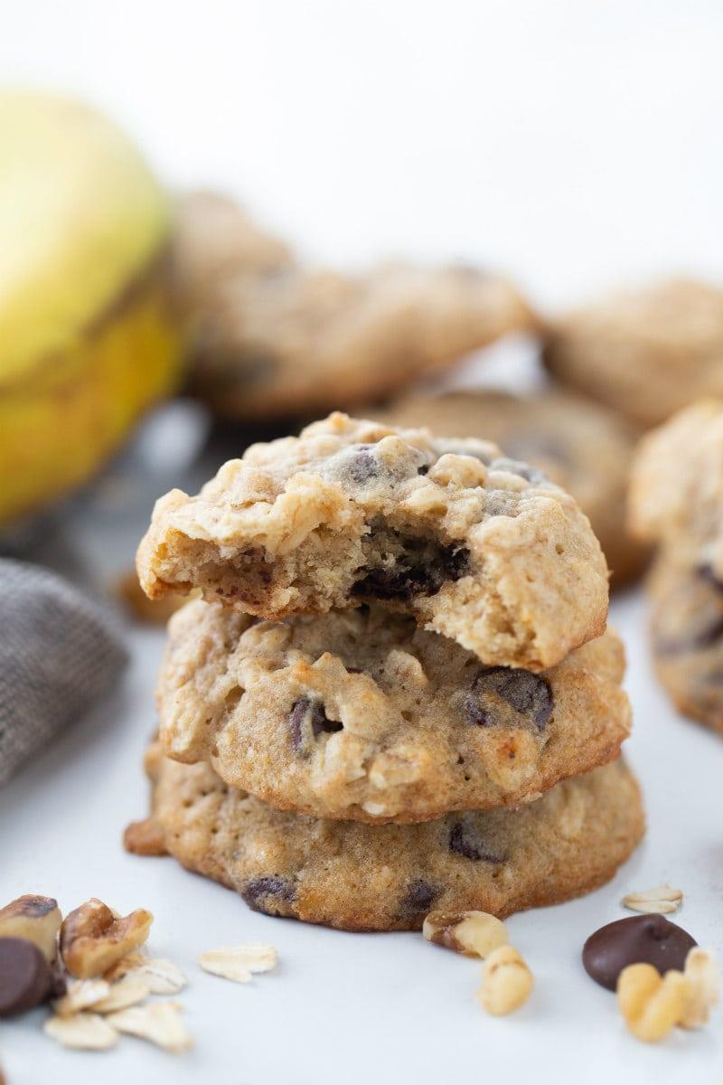 three stacked banana walnut chocolate chip cookies with peek of a banana in the background