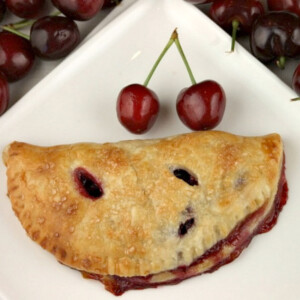 fresh cherry turnover on a white plate with a couple of fresh cherries on the plate. fresh cherries in the background