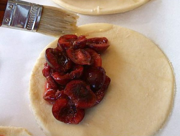 showing process of making cherry turnovers with cherry filling on a pastry and using a brush to brush edges with water