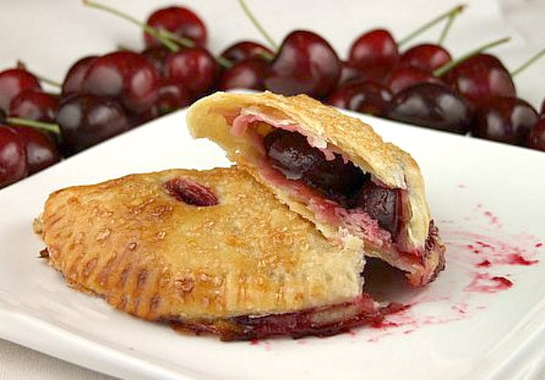 two cherry turnovers on a white plate with one cut open to see the inside. Fresh cherries in the background