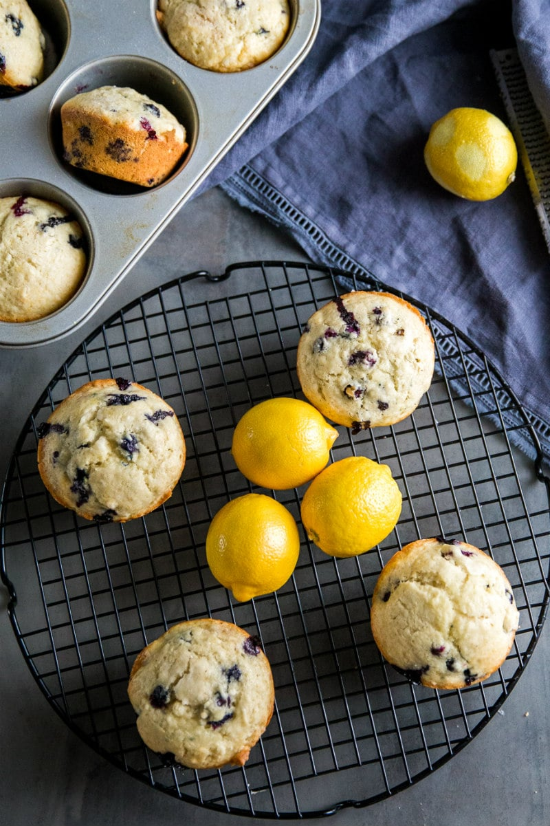 overhead shot of lemon blueberry muffins on a cooling rack with fresh lemons. muffins in a muffin pan on the side, and a blue cloth napkin displayed.