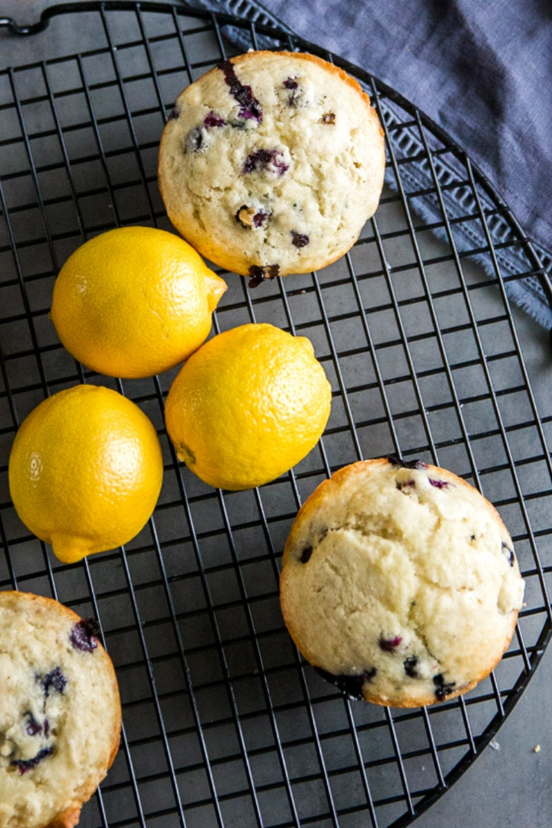 overhead shot of lemon blueberry muffins on a cooling rack with fresh lemons