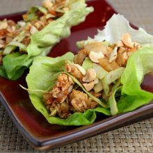 two sweet and spicy lettuce wraps on a burgundy plate