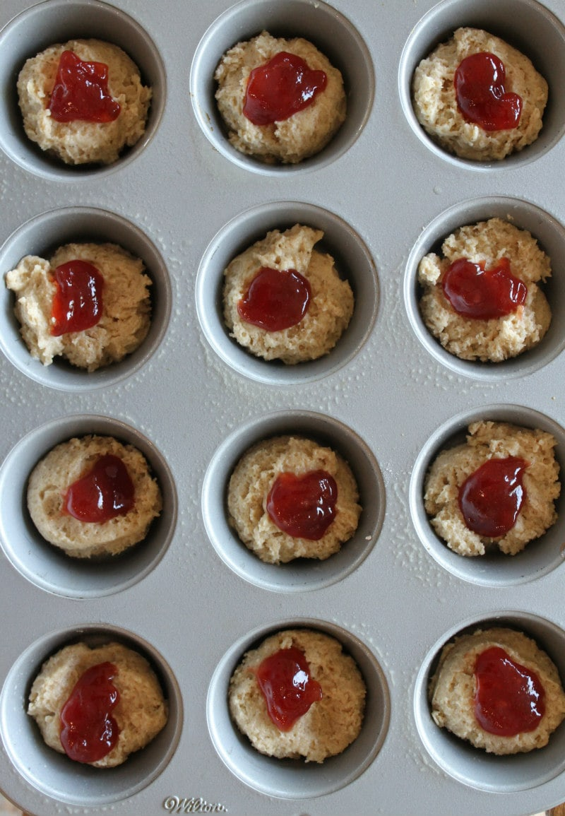 overhead shot of strawberry cinnamon muffin batter with strawberry jam in a muffin tin