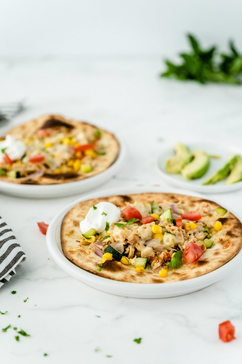 two white plates with chicken and summer vegetable tostadas with a small white plate of sliced avocado in the background and a blue/white striped napkin peeking in on the side