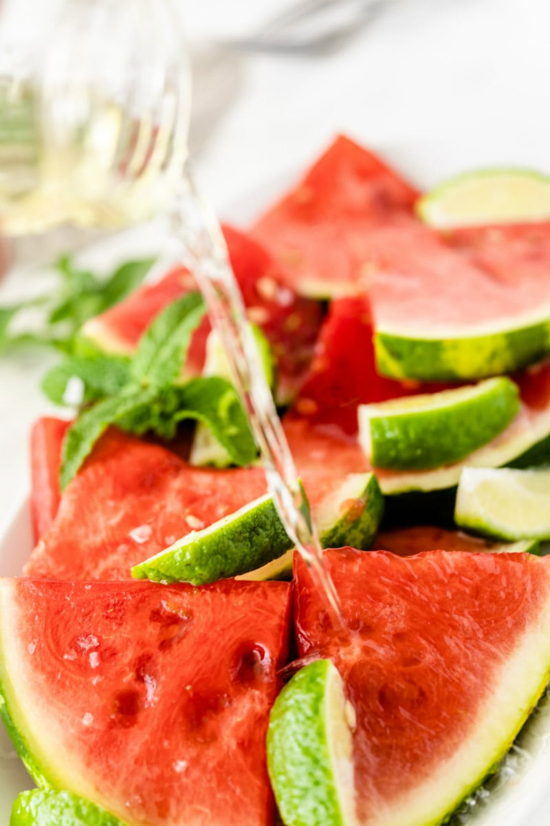 pouring tequila onto watermelon with lime wedges