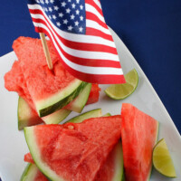 tequila soaked watermelon wedges on a white platter with lime wedges and an american flag stuck into the top