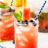 watermelon tequila cocktails in mason jars garnished with fresh blueberries and mint. striped straws. bottle of tequila in the background