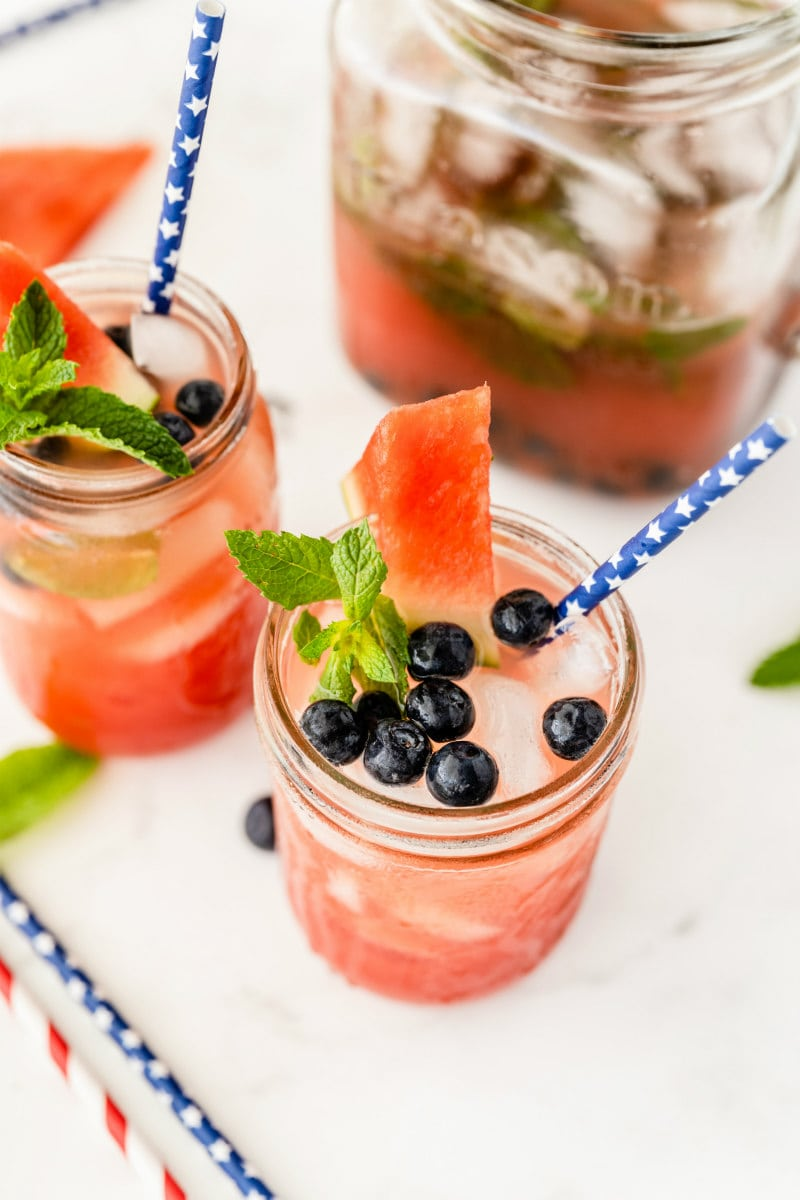 watermelon tequila cocktails in mason jars. garnished with blueberries and fresh mint and watermelon wedges. striped straws.