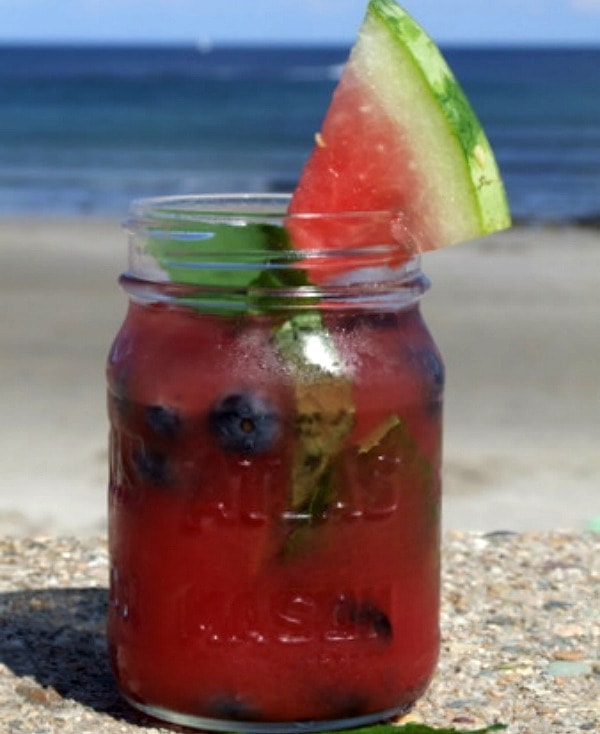 watermelon tequila cocktail in a mason jar with watermelon wedge garnish. beach view in the background