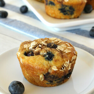 Blueberry Cinnamon Muffin on a white plate with more muffins on a platter in the background with a white and blue striped napkin