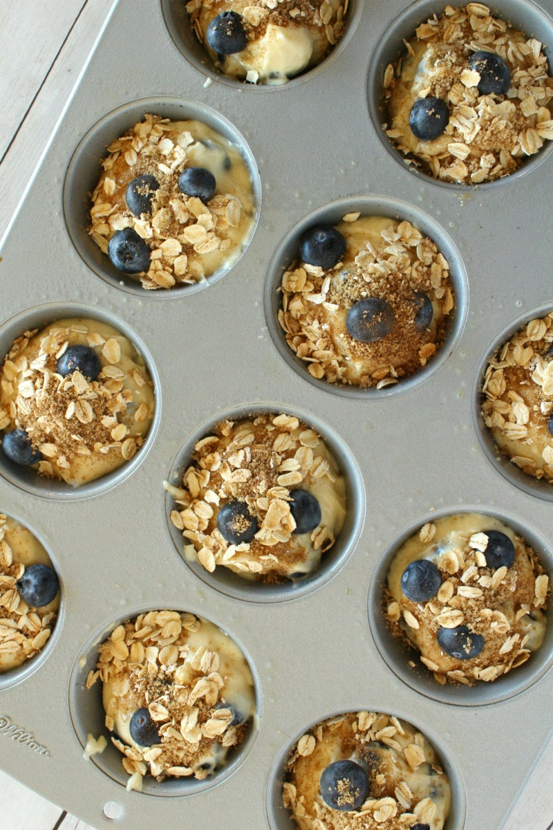 making blueberry cinnamon muffins batter in muffin pan