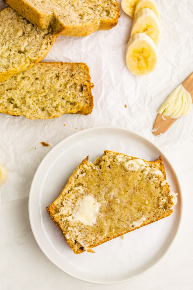 Slice of banana bread on white plate with melting butter