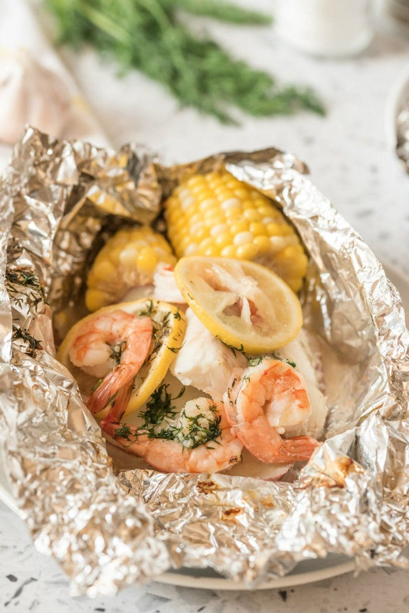 grilled new england seafood foil packets opened up to see the inside. fresh herbs in background