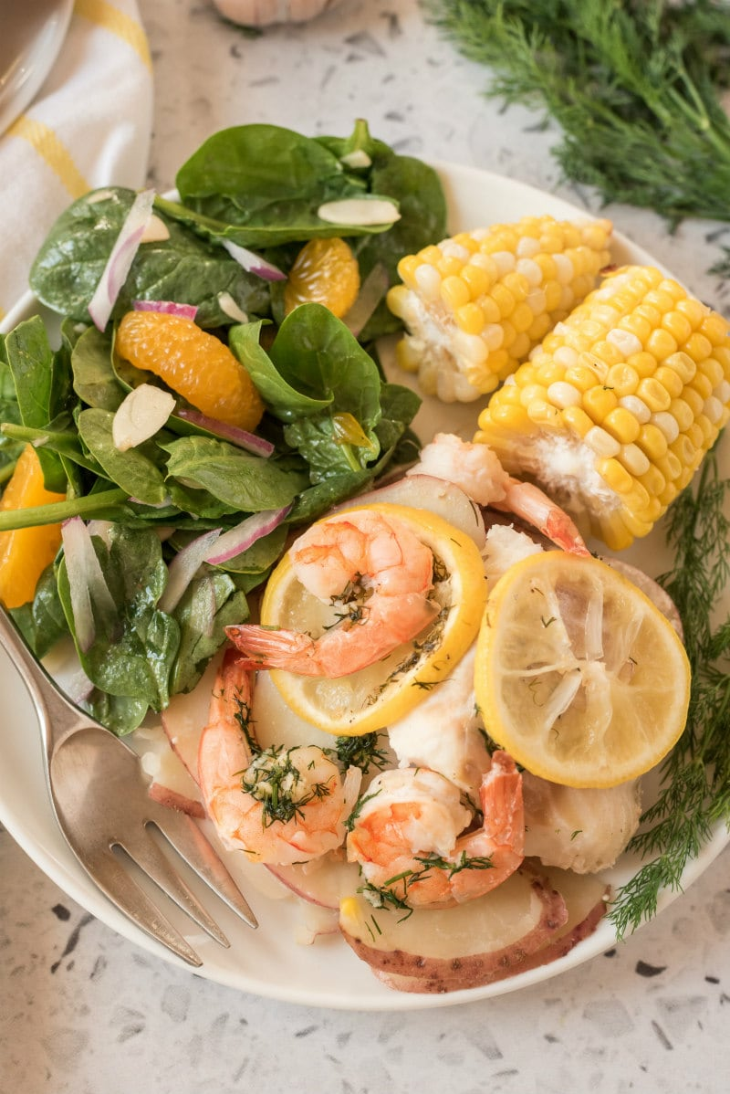 seafood and corn on a white plate with salad and a fork