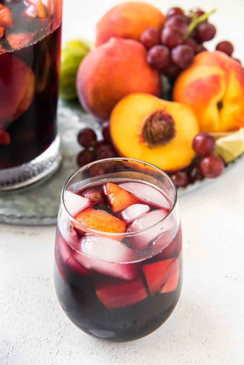 glass of red wine sangria with pitcher in the background and grapes and peaches