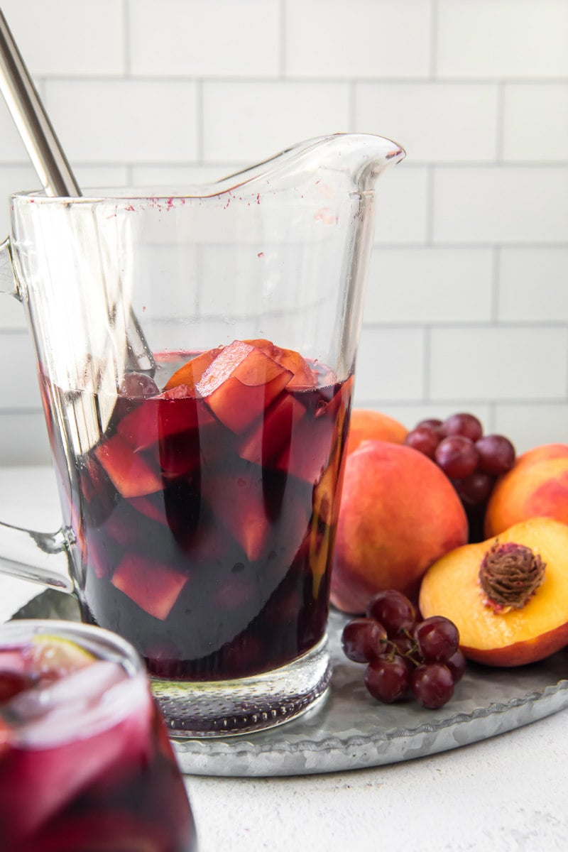 pitcher of red wine sangria with a stirring spoon inside. Grapes and peaches on the side