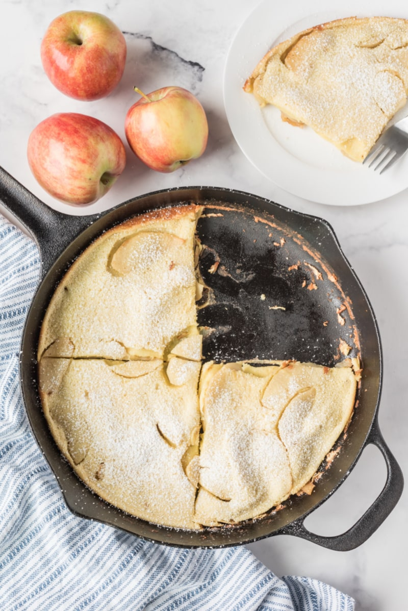 big apple pancake in cast iron skillet with piece cut out of it
