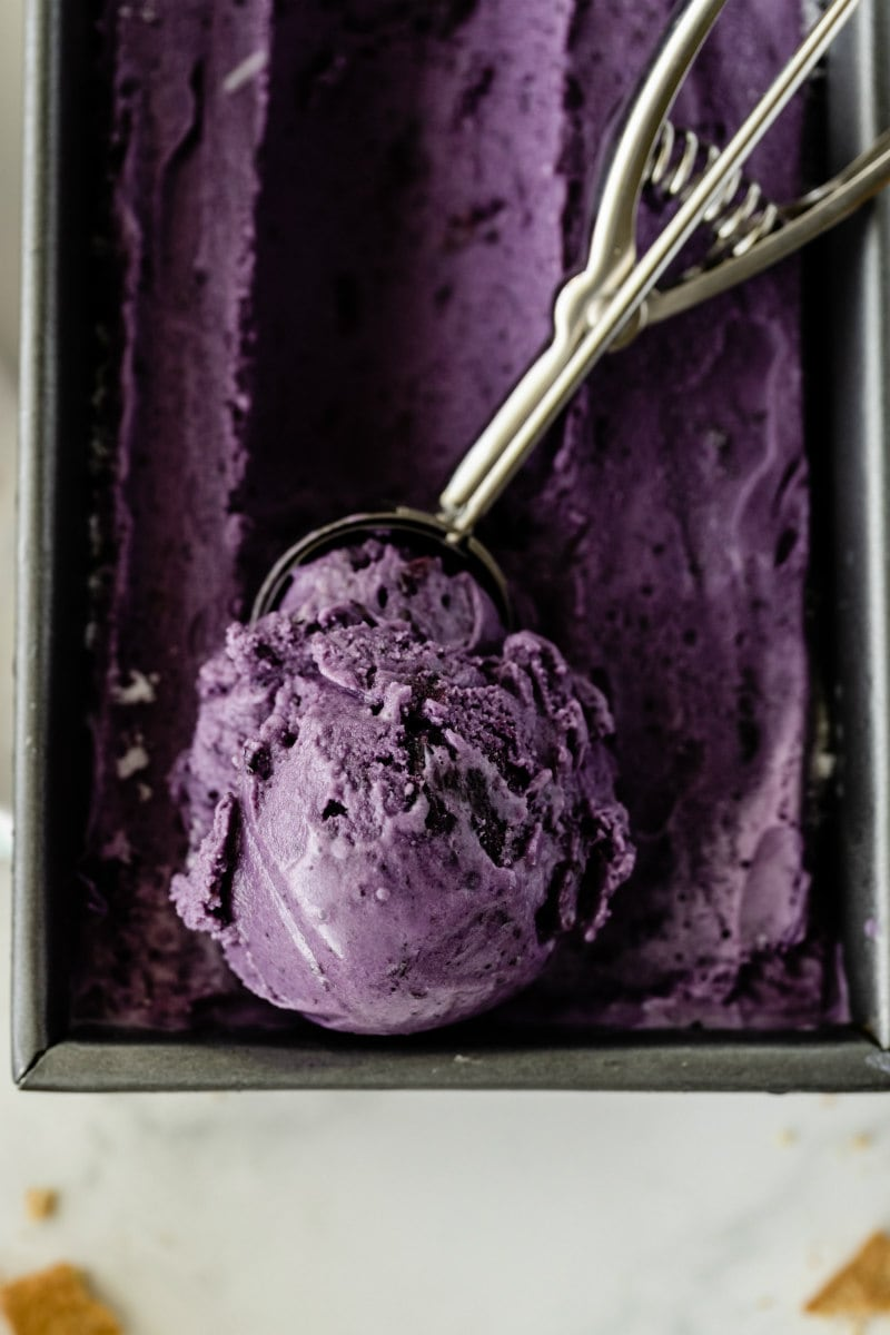 rectangular metal tub of blueberry cheesecake ice cream with an ice cream scoop that has scooped up some of the ice cream sitting on top of the tub