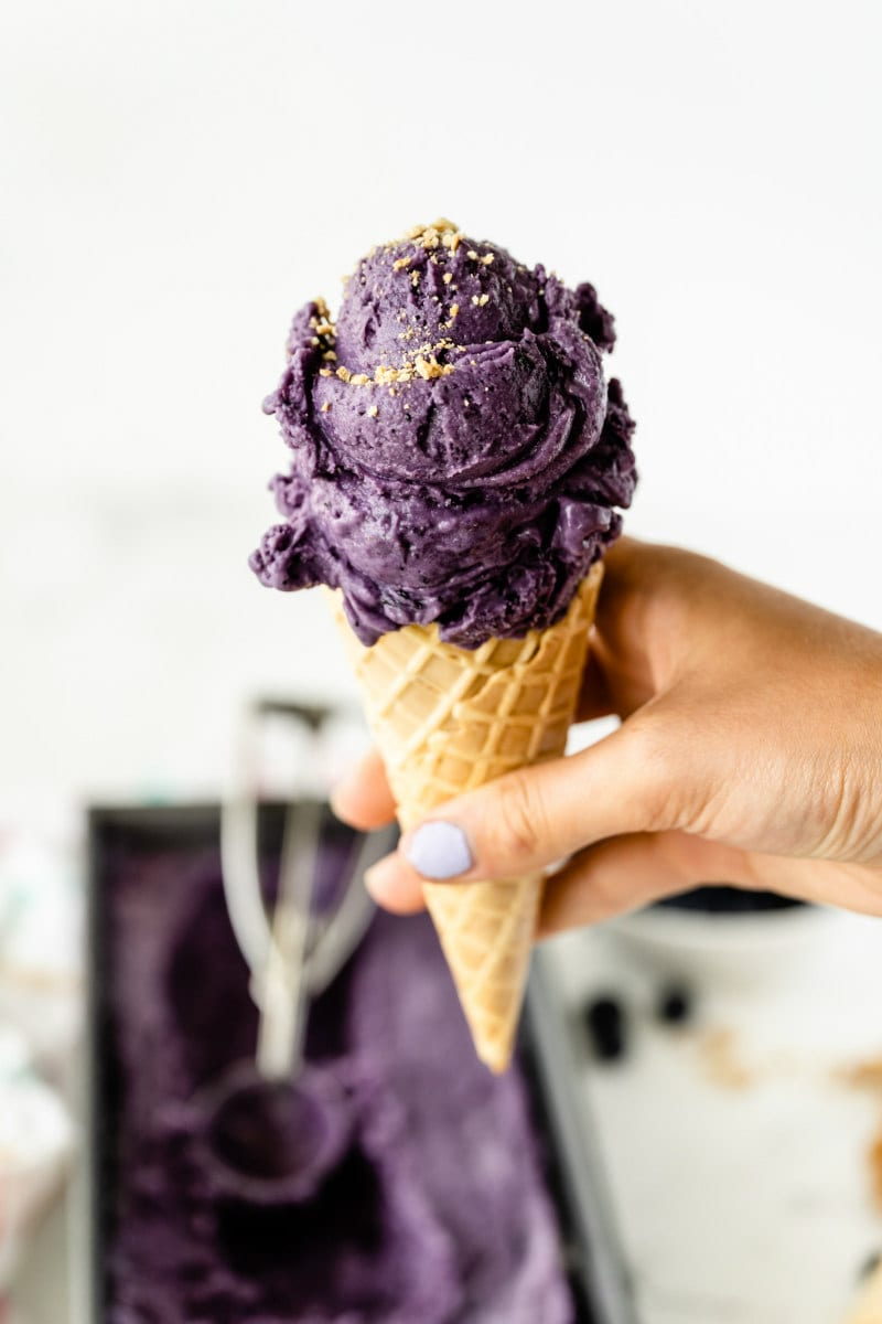 hand holding an ice cream cone with one scoop of blueberry cheesecake ice cream on top