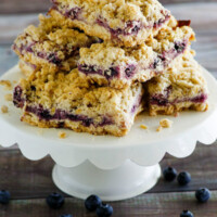 lemon blueberry streusel bars stacked on a white display platter with a wood background