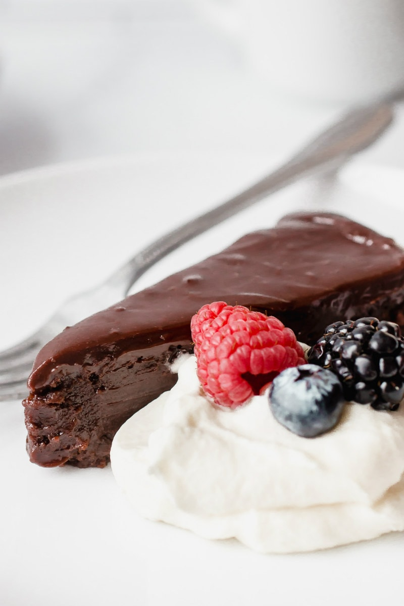 slice of chocolate truffle cake served with cream and berries