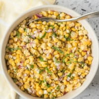 overhead shot of fresh corn salad in a white bowl with a serving spoon. light yellow napkin displayed on the side