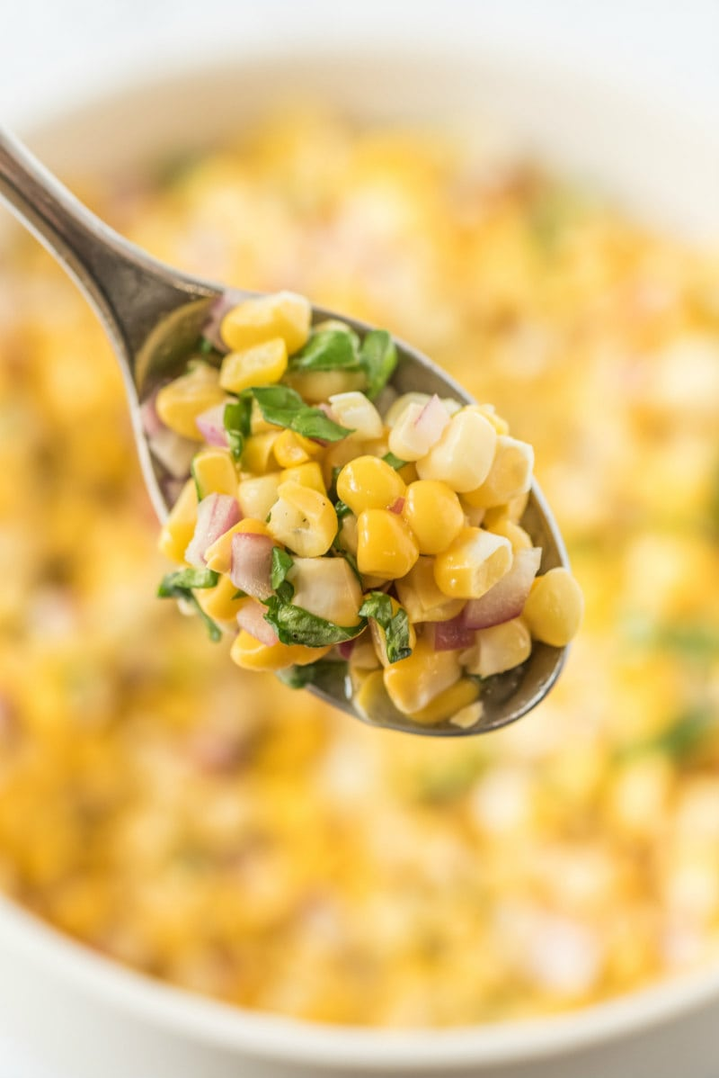 spoonful of fresh corn salad above a white bowl of corn salad