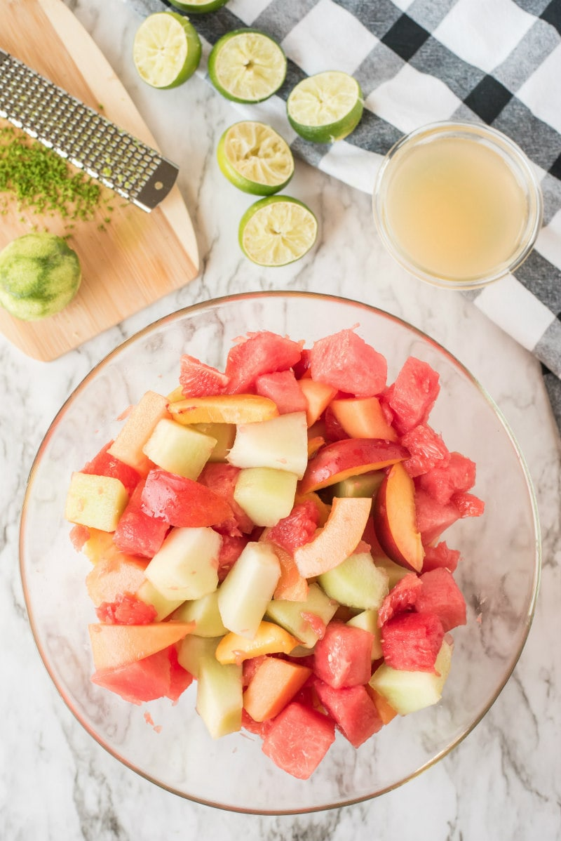 overhead shot of preparation of fruit salad with lime syrup. fruit in glass bowl and zested limes and lime juice in the background