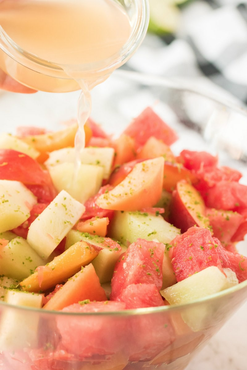 cup pouring lime syrup onto fruit salad in glass bowl