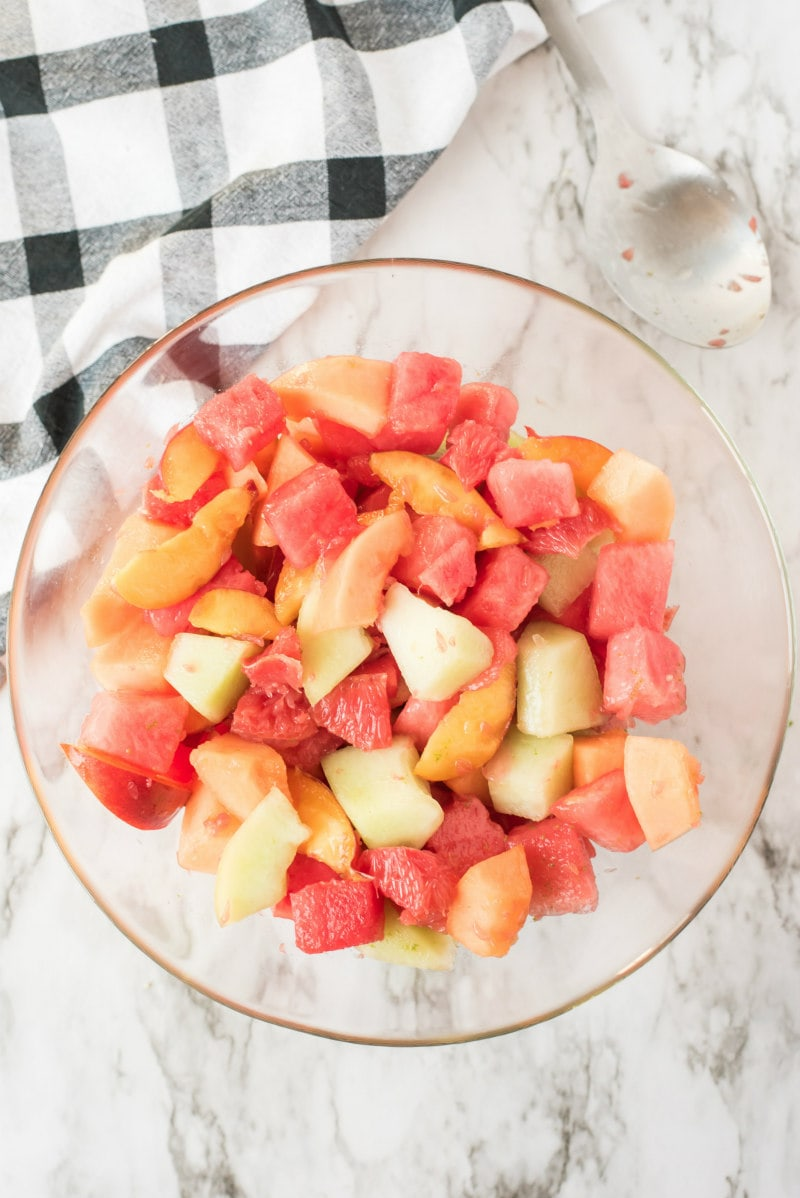 overhead shot of fruit salad in a glass bowl with black and white napkin in background