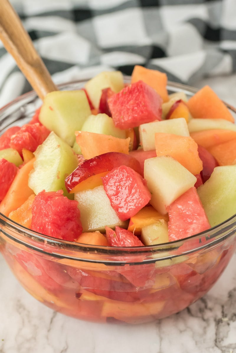 fruit salad with lime syrup in a glass bowl with a wooden spoon. black and white napkin in background.