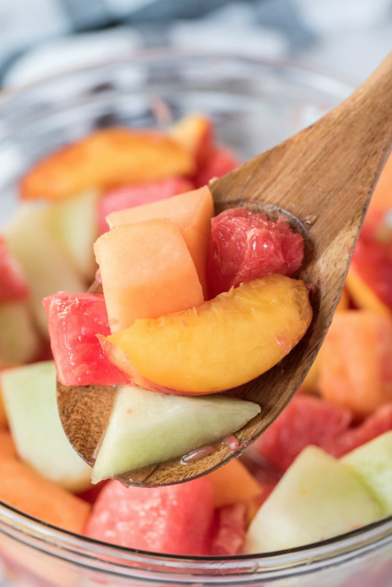 close up of fruit salad in a glass bowl with a wooden spoon