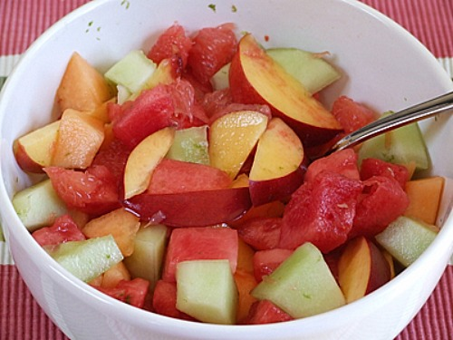 fruit salad in a white bowl with a spoon