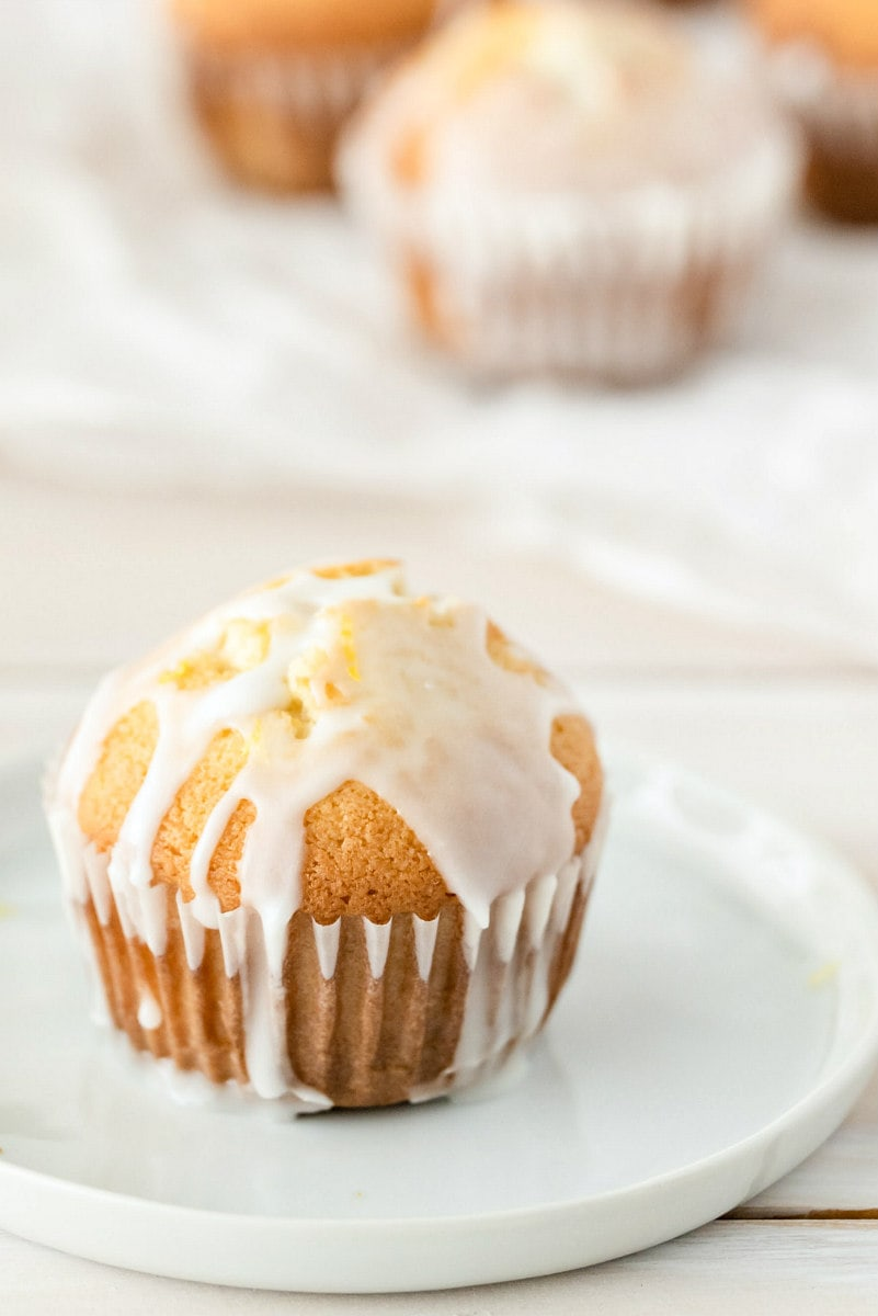 lemon pound cake muffin with glaze sitting on a white plate with more muffins in the background