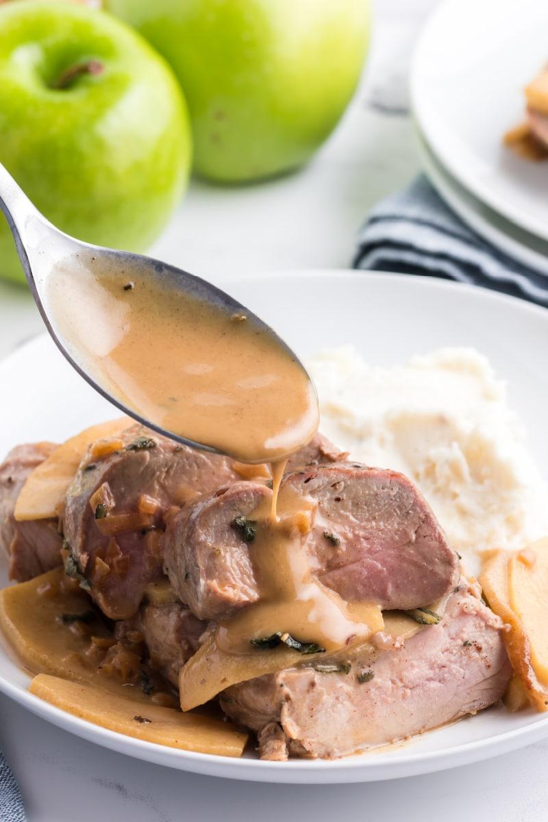 spooning sauce over pork tenderloin