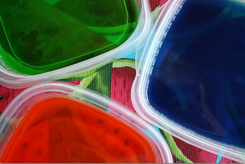 three plastic tubs of jello - green, blue and red